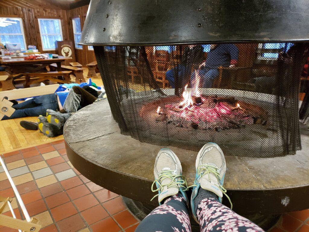 A camper enjoys keeping their feet warm near the fireplace
